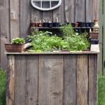 Gemüsetheke der Marke Eigenbau. Das Hochbeet aus rustikalen Holzbohlen mit Extraablage für Anzuchttöpfe fügt sich nahtlos an den Gartenschuppen.