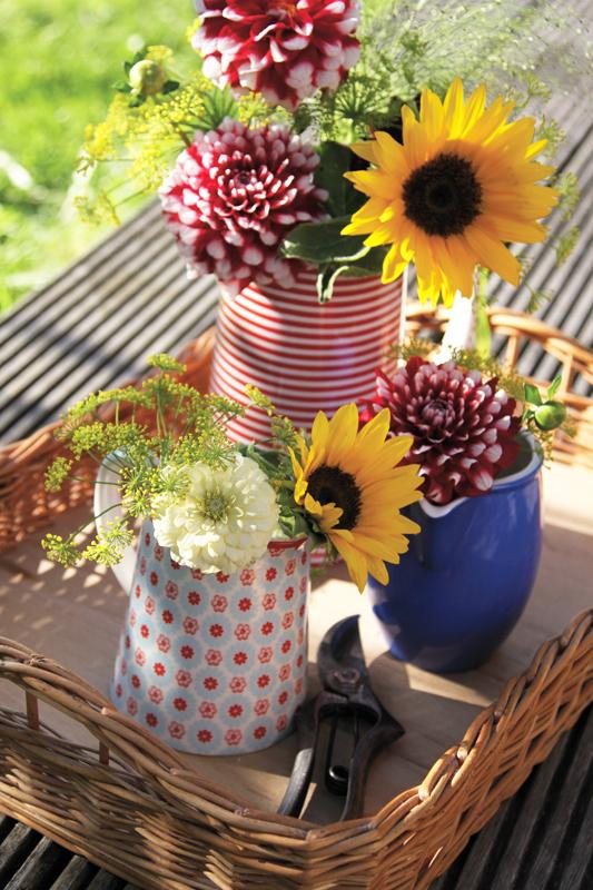 Es müssen nicht immer aufwendige Blumengestecke sein, auch ein paar Blüten-Stiele auf mehrere kleine Vasen verteilt ergeben ein hübsches Ensemble.
